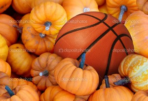Thanksgiving Day basketball and autumn sports during harvest time with a holiday tournament ball in a pile of orange pumpkins as a concept for living a healthy lifestyle and eating natural food with fitness through exercise.
